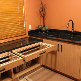 Dedicated laundry room - mid-sized zen l-shaped ceramic tile dedicated laundry room idea in Calgary with an undermount sink, flat-panel cabinets, light wood cabinets, granite countertops, orange walls and a side-by-side washer/dryer