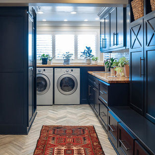 Utility room - mid-sized transitional galley porcelain floor and gray floor utility room idea in Kansas City with shaker cabinets, wood countertops, beige walls, a side-by-side washer/dryer, brown countertops and black cabinets