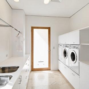 Свежая идея для дизайна: параллельная универсальная комната среднего размера в современном стиле с двойной раковиной, столешницей из кварцевого агломерата, полом из известняка и со стиральной и сушильной машиной рядом - отличное фото интерьера