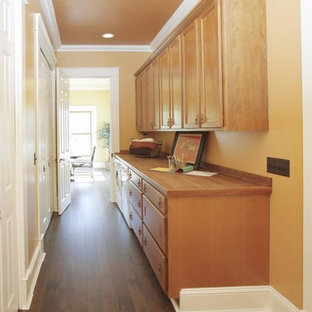 Large victorian galley utility room in Grand Rapids with flat-panel cabinets, medium wood cabinets, wood worktops, dark hardwood flooring, a side by side washer and dryer and orange walls.