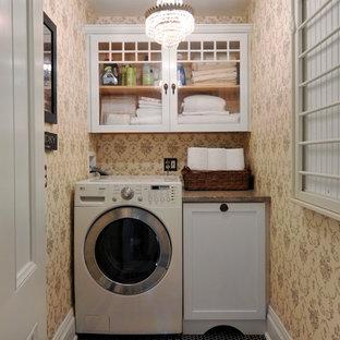 Cette photo montre une petit buanderie linéaire victorienne dédiée avec un placard à porte shaker, un plan de travail en granite, un sol en carrelage de porcelaine, un mur beige et des portes de placard blanches.