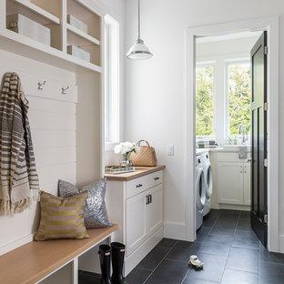 Inredning av ett klassiskt mellanstort linjärt grovkök, med vita skåp, laminatbänkskiva, vita väggar, klinkergolv i keramik, en tvättmaskin och torktumlare bredvid varandra, skåp i shakerstil och svart golv