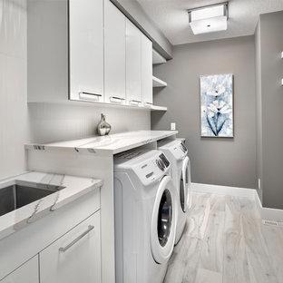 Immagine di una grande sala lavanderia contemporanea con lavello sottopiano, ante a persiana, ante bianche, top in quarzo composito, pareti grigie, pavimento in gres porcellanato, lavatrice e asciugatrice affiancate, pavimento grigio e top bianco