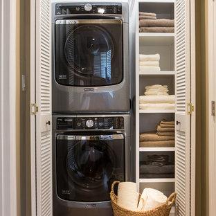 Exemple d'une petit buanderie linéaire chic avec un placard, un placard sans porte, des portes de placard blanches, un mur blanc, un sol en bois brun et des machines superposées.