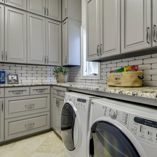 Photo of a large mediterranean u-shaped utility room in Austin with a submerged sink, raised-panel cabinets, grey cabinets, granite worktops, grey walls, travertine flooring and a side by side washer and dryer.