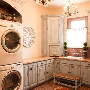Lantlig inredning av en mellanstor beige l-formad beige tvättstuga enbart för tvätt, med en nedsänkt diskho, luckor med upphöjd panel, skåp i slitet trä, träbänkskiva, beige väggar, tegelgolv, en tvättpelare och rött golv