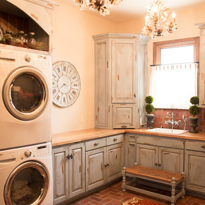 Dedicated laundry room - mid-sized farmhouse l-shaped brick floor and red floor dedicated laundry room idea in Oklahoma City with a drop-in sink, raised-panel cabinets, distressed cabinets, wood countertops, beige walls, a stacked washer/dryer and beige countertops