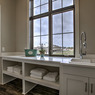 Design ideas for a large farmhouse single-wall separated utility room in Omaha with a built-in sink, quartz worktops, porcelain flooring, a side by side washer and dryer, white cabinets, recessed-panel cabinets, grey walls and grey floors.