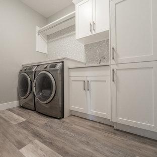 Foto på en stor vintage linjär tvättstuga enbart för tvätt, med en dubbel diskho, luckor med infälld panel, vita skåp, bänkskiva i koppar, grå väggar, vinylgolv, en tvättmaskin och torktumlare bredvid varandra och flerfärgat golv