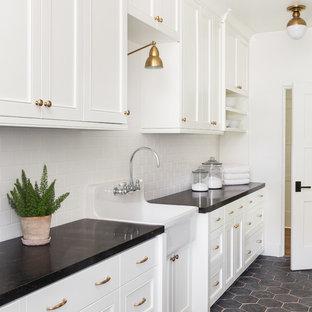Idee per una sala lavanderia classica con lavello stile country, ante con riquadro incassato, ante bianche, pareti bianche, pavimento grigio e top nero