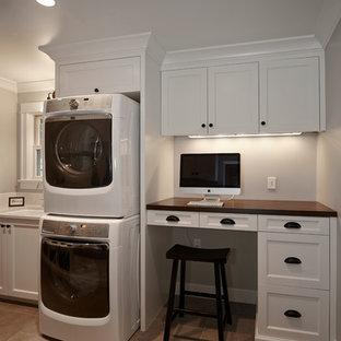 Inredning av ett klassiskt stort parallellt grovkök, med en undermonterad diskho, luckor med infälld panel, vita skåp, träbänkskiva, grå väggar, en tvättpelare, travertin golv och brunt golv