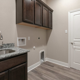 Design ideas for a large arts and crafts utility room in Austin with an undermount sink, recessed-panel cabinets, dark wood cabinets, granite benchtops, beige walls, vinyl floors, a side-by-side washer and dryer, brown floor and multi-coloured benchtop.