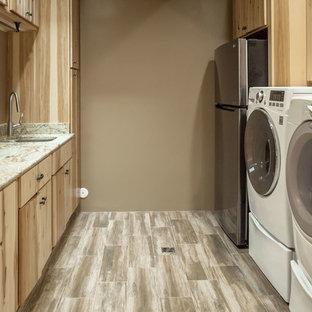 Inredning av ett klassiskt l-format grovkök, med en undermonterad diskho, luckor med profilerade fronter, skåp i ljust trä, granitbänkskiva, bruna väggar, klinkergolv i keramik och en tvättmaskin och torktumlare bredvid varandra
