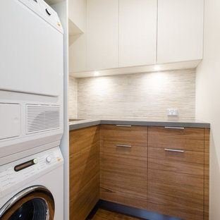 Small trendy u-shaped plywood floor utility room photo in Melbourne with flat-panel cabinets, medium tone wood cabinets, quartz countertops, beige walls, a stacked washer/dryer and an undermount sink