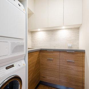 Immagine di una piccola lavanderia multiuso minimal con ante lisce, ante in legno scuro, top in quarzo composito, pareti beige, pavimento in compensato, lavatrice e asciugatrice a colonna e lavello sottopiano