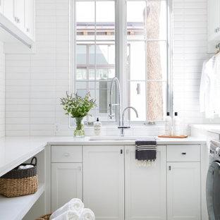 Ispirazione per una lavanderia multiuso mediterranea con lavello sottopiano, ante in stile shaker, ante bianche, pareti bianche, pavimento con piastrelle in ceramica, pavimento beige e top bianco