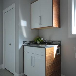Idee per una sala lavanderia moderna con lavello sottopiano, ante lisce, ante bianche, top in quarzite e pareti grigie