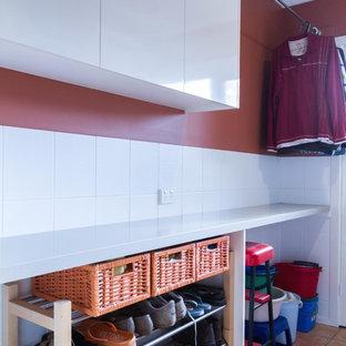 Esempio di una piccola lavanderia multiuso moderna con ante lisce, ante bianche, top in quarzo composito, pavimento con piastrelle in ceramica e pavimento arancione