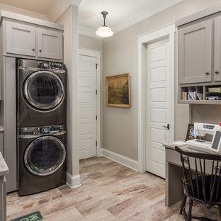 Idee per una sala lavanderia country di medie dimensioni con lavello sottopiano, ante con riquadro incassato, ante grigie, top in granito, lavatrice e asciugatrice a colonna e pareti beige