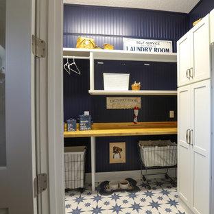 Inspiration pour une petit buanderie rustique dédiée avec un placard à porte shaker, des portes de placard blanches, un plan de travail en bois, une crédence bleue, une crédence en lambris de bois, un mur bleu, un sol en carrelage de porcelaine, des machines superposées, un sol bleu, un plan de travail blanc et du lambris.