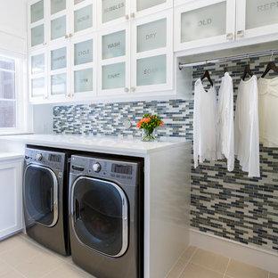 Exemple d'une buanderie tendance en L avec un placard à porte vitrée, des portes de placard blanches, un mur multicolore, un sol en carrelage de céramique, des machines côte à côte et un plan de travail blanc.