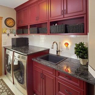 Esempio di una sala lavanderia country di medie dimensioni con lavello da incasso, ante con riquadro incassato, ante rosse, top in granito, pareti beige, pavimento in gres porcellanato, lavatrice e asciugatrice affiancate e pavimento beige