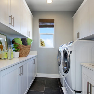 Inspiration for a transitional galley black floor laundry room remodel in Orange County with shaker cabinets, white cabinets, gray walls, a side-by-side washer/dryer and white countertops