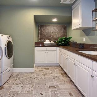 Idee per una sala lavanderia chic con lavello sottopiano, ante con bugna sagomata, ante bianche, pareti verdi, lavatrice e asciugatrice affiancate e top marrone