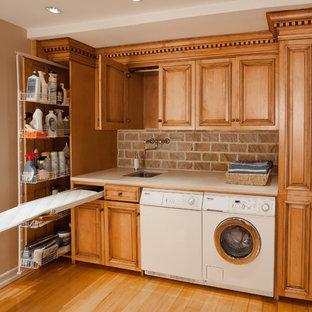 Foto di una piccola lavanderia multiuso classica con lavello a vasca singola, ante con bugna sagomata, parquet chiaro, lavatrice e asciugatrice affiancate, ante in legno scuro, top in granito, pareti multicolore, pavimento marrone e top beige