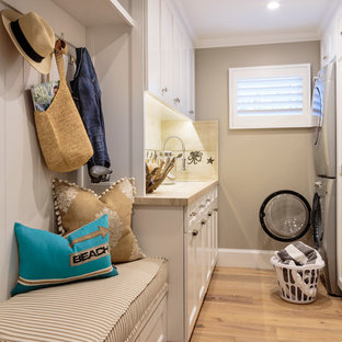 Photo of a large beach style galley dedicated laundry room in Orange County with a single-bowl sink, recessed-panel cabinets, white cabinets, limestone benchtops, grey walls, light hardwood floors and a stacked washer and dryer.