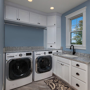 Mid-sized country l-shaped utility room in Other with a single-bowl sink, recessed-panel cabinets, white cabinets, granite benchtops, blue walls, marble floors, a side-by-side washer and dryer, grey benchtop and multi-coloured floor.