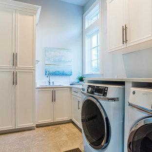 Ispirazione per un'ampia sala lavanderia shabby-chic style con lavello da incasso, ante in stile shaker, ante bianche, top in granito, pareti grigie, lavatrice e asciugatrice affiancate, pavimento beige e top bianco