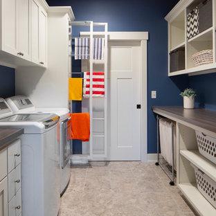 Foto di una lavanderia multiuso stile americano di medie dimensioni con ante lisce, ante bianche, top in laminato, pareti blu, lavatrice e asciugatrice affiancate, top grigio e lavatoio