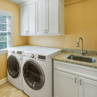 Idéer för små vintage linjära tvättstugor enbart för tvätt, med en undermonterad diskho, luckor med infälld panel, vita skåp, bänkskiva i kvarts, klinkergolv i porslin, en tvättmaskin och torktumlare bredvid varandra och orange väggar