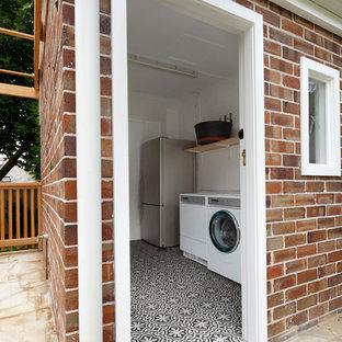 Exemple d'une grand buanderie chic en L avec un évier encastré, un placard à porte shaker, des portes de placard blanches, un plan de travail en quartz modifié, une crédence bleue, une crédence en carreau de céramique et un sol en bambou.