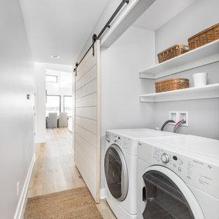 Immagine di un ripostiglio-lavanderia stile marino con pareti grigie, parquet chiaro, lavatrice e asciugatrice affiancate e pavimento beige