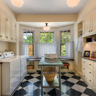Photo of a traditional galley dedicated laundry room in Philadelphia with beaded inset cabinets, beige cabinets, beige walls, painted wood floors, a side-by-side washer and dryer and multi-coloured floor.