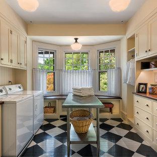 Esempio di una sala lavanderia tradizionale con ante a filo, ante beige, pareti beige, pavimento in legno verniciato, lavatrice e asciugatrice affiancate e pavimento multicolore