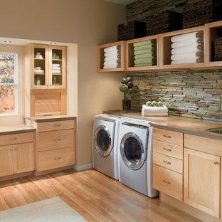 Immagine di una grande sala lavanderia tropicale con lavello sottopiano, ante in stile shaker, ante in legno chiaro, top in superficie solida, pareti beige, pavimento in legno massello medio e lavatrice e asciugatrice affiancate