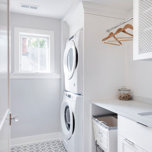 Inspiration for a small transitional single-wall ceramic tile and multicolored floor dedicated laundry room remodel in Minneapolis with a stacked washer/dryer, an undermount sink, shaker cabinets, white cabinets, gray walls and white countertops
