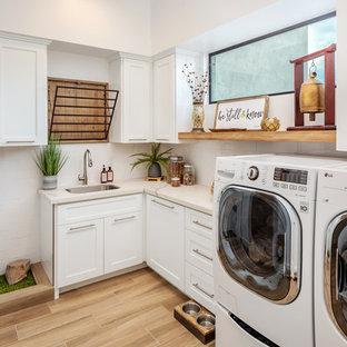 Immagine di una lavanderia multiuso tradizionale con lavello sottopiano, ante in stile shaker, ante bianche, pareti bianche, lavatrice e asciugatrice affiancate, pavimento beige e top bianco