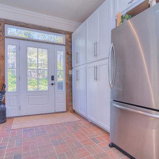 Foto di una lavanderia country con lavello integrato, ante in stile shaker, ante bianche, top in acciaio inossidabile, pavimento in mattoni e lavatrice e asciugatrice a colonna