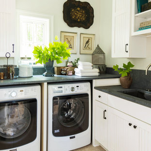 Transitional l-shaped beige floor dedicated laundry room photo in New York with an undermount sink, white cabinets, white walls and gray countertops