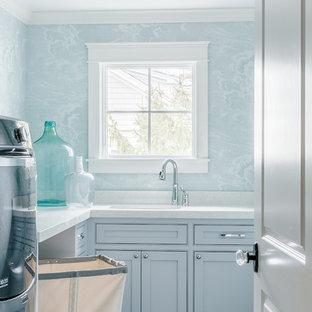 Bild på en lantlig tvättstuga enbart för tvätt, med en undermonterad diskho, bänkskiva i kvarts, klinkergolv i keramik, en tvättmaskin och torktumlare bredvid varandra och blå väggar