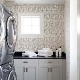 This is an example of a coastal separated utility room in Portland Maine with shaker cabinets, grey cabinets, multi-coloured walls, a stacked washer and dryer, multi-coloured floors and black worktops.