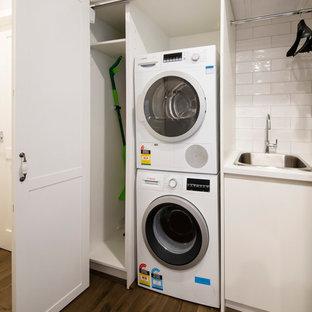 Idéer för en liten klassisk vita linjär liten tvättstuga, med en nedsänkt diskho, vita skåp, bänkskiva i kvarts, grå väggar, laminatgolv, en tvättpelare och skåp i shakerstil
