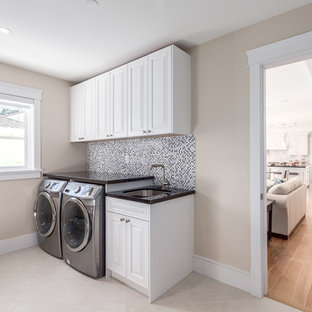 Inspiration for a large classic single-wall separated utility room in Vancouver with white cabinets, beige walls, a side by side washer and dryer, a submerged sink, raised-panel cabinets, granite worktops and travertine flooring.