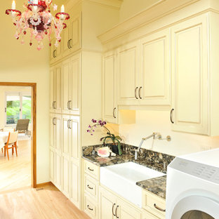 Inspiration for a large eclectic galley separated utility room in Other with a belfast sink, raised-panel cabinets, yellow cabinets, granite worktops, yellow walls, light hardwood flooring and a side by side washer and dryer.