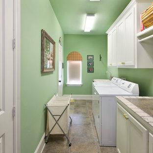 Idéer för mellanstora vintage linjära tvättstugor enbart för tvätt, med luckor med infälld panel, vita skåp, kaklad bänkskiva, gröna väggar och en tvättmaskin och torktumlare bredvid varandra