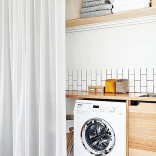 Idéer för att renovera ett litet minimalistiskt beige linjärt beige grovkök, med en nedsänkt diskho, släta luckor, skåp i mellenmörkt trä, träbänkskiva, vita väggar, målat trägolv, en tvättmaskin och torktumlare bredvid varandra och vitt golv